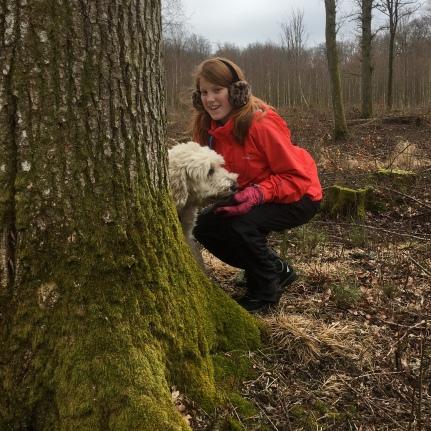 Lycklig Charlie hittar Linnea bakom ett stort träd.